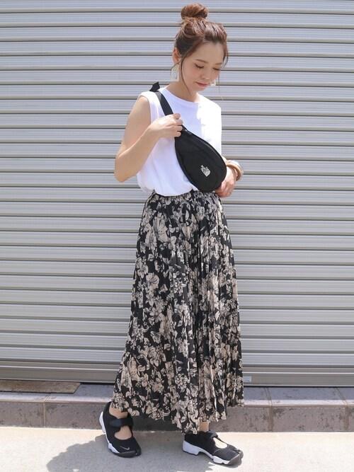白いTシャツと花柄プリーツスカートと黒いスニーカーサンダルのコーデ