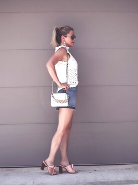 "Erin is wearing HENRI BENDEL ""Stanton Mini Studded Crossbody with Woven Strap"""